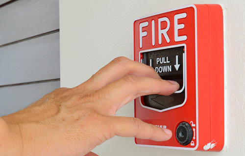 hand pulling down the handle of a wall mounted fire alarm